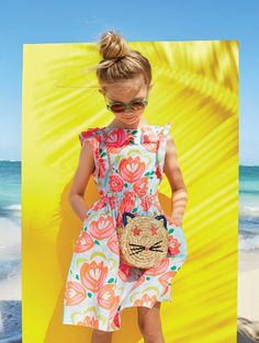 crewcuts girls' ruffle dress in cactus floral, round sunnies and woven straw cat bag.