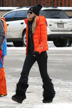 Snow bunny: Looking the ultimate snow bunny on her pre-Christmas holiday, the catwalk queen, 51, opted for a chic winter look in a bright orange padded jacket and slim-fitting black trousers