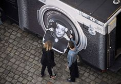 A teenager looks at her portrait after she was photographed in the truck (background) belonging to French street-artist and photographer JR, in La Rochelle, western France. The artist plans to print the portraits of anonymous people on a tarp which will cover the Paris Pantheon, a secular temple which contains the remains of distinguished French citizens, during renovation works.
