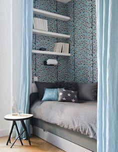 Des rideaux bleus pour délimiter un coin canapé-lit dans le salon
