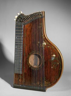 "*1867 German (Munich) Zither at the Victoria and Albert Museum, London - From the curators' comments: ""The Alpine zither was developed by Johan Petzmayer (1803 - 1884) in Munich during the 1820s. The musician would set it on a table and press the five highest strings down onto a fretted finger board with his left hand, and pluck them with the thumb and index finger of his right hand, strumming the other bass strings with his middle and ring finger as required."""