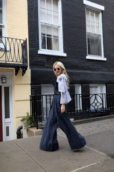 Blair Eadie of Atlantic-Pacific wearing a pinstripe jumpsuit, Burberry coat, Gucci logo belt and black pumps to NYFW.