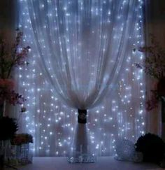 Christmas lights behind shear drapes, but not pulled together and with warm white lights!