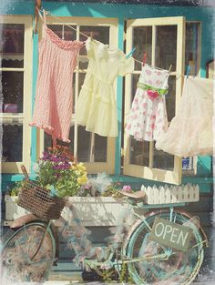 pretty dresses on clothesline...and the bike, and the sign, and the open window ane the flowers in the white wooden picket boxes.....I love everything about this picture!