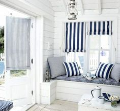 Interior design coastal beach style guest room cabin bungalow pool room for summer: white wooden slat walls, exposed beam ceiling, window seat, navy white stripe upholstery nautical style shabby chic