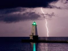A bolt of lightning lights up Lake Michigan behind the north pierhead in Ludington as a mid-July thunderstorm comes in from the west. Ludington Michigan, Lake Michigan, Grands Lacs, Costa, Beacon Of Light, Le Moulin, Great Lakes, Windmill, Beautiful Landscapes