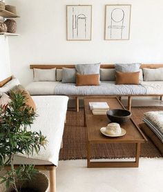 a comfy living room with a white backdrop and wooden furniture of various stains   darker and lighter ones