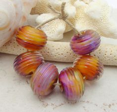 set of lampwork glass beads with purple silver glass over a yellow-orange base encased under clear. Some of the beads in this set have more purple than the others. They have a ridged texture. <3<3<3 @