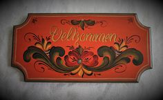 Beautiful Norwegian Rosemaling Velkommen Plaque, done in the Romsdal Style. Painted on a 5 x 10 bass wood Plaque. Background colors are a antiqued Red Oxide (BM), and Telemark Green, with anitquing around the edge and back. Hand painted lettering reading Velkommen in Norwegian.