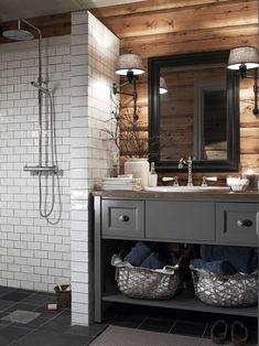KONTRASTER: De blanke flisene mot det røffe treverket gir en spennende miks av materialer på badet i denne hytta. Baderomsinnredningen er laget av en møbelsnekker, fargen er True Stone fra Nordsjø.