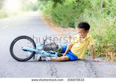 Young Asian boy got accident and fall from the bicycle and feel pain. Transportation and safety concept.
