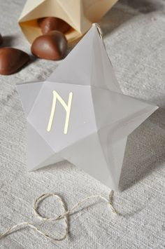 """DIY 3D paper stars from L'Art de la Curiosité: des étoiles pour l'Avent. With links to free template and instructions. This one is made of vellum and four stars together spell """"Noel"""" (Christmas). You can hang them in front of a mirror or window. You can also use these as boxes for small treats."""