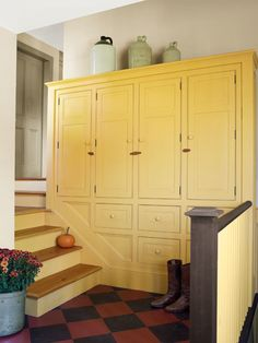 A set of descending built-ins, finished with wood clasps, provides coat and boot storage in this farmhouse mudroom.