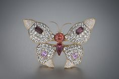 This butterfly brooch is set with red and pink topaz from Russia, Pakistan and Brazil, along with rainbow feldspars from Magadascar, colorless diamonds and colorless jeremijevites for the eyes. Although most people think topaz is only a yellow gem, in nature most topaz is colorless to pale blue. Topaz gems in shades of deep pink to red are the most prized.