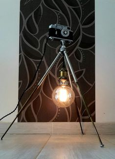 70's Tripod Antique Floor Lamp with Camera Dimmer - Floor Lamps -   A vintage tripod and an antique soviet camera, converted into a beautiful antique floor lamp. The lens of the camera works as dimmer – turning left to right, the brightness of the bulb can easily be adjusted. The height is adjustable between 50 and 130cm, and the 12cm Edison bulb can be... #Antique #Camera #Edison #Handmade #Lightbulb #Metal #Recycled #Retro #Steampunk #Vintage