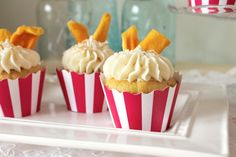Coconut Mango Cupcakes filled with mango preserves, frosted with a simple buttercream, garnished with a sprinkle of toasted coconut & a couple of slices of dried mango. Happiness in a single bite! #cupcake #recipe