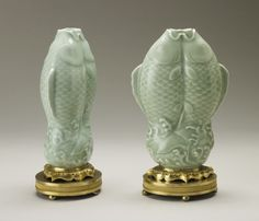 A pair of double fish pale green Chinese celadon porcelain vases, each in the form of two leaping carps, on a French gilt bronze pedestal supported on four ball feet.
