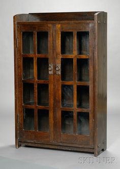 Gustav Stickley Double-Door Bookcase  Oak  New York, c. 1902-03  Rectangular gallery top with through tenons over two double doors divided by sixteen panes, with ring pulls, dark finish.