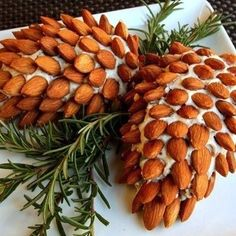 Pinecone Cheese Balls:  Use almonds or pecans. Christmas entertaining. Here is the recipe: One 8 oz container garden vegetable cream cheese, One 8 oz container roasted garlic cream cheese, 1 cup grated sharp cheddar cheese, 3 chopped green onions. For decoration: 2 cups pecan halves or almonds, rosemary sprigs.