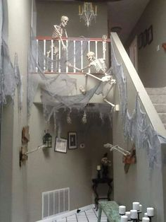 Halloween decorations - skeletons climbing staircase with cobwebs.
