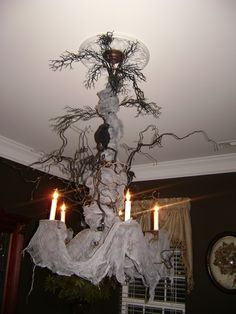creepy Halloween Chandelier. Very cool. Cheesecloth, dried branches spray painted black and some crows and spiders....
