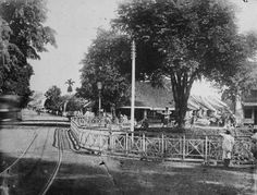 1870-1900: Jembatan Kramat, Batavia. Di latar belakang, di belakang orang yang berdiri dekat pohon, tertulis papan nama penjahit A. Kim