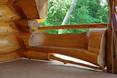 Clever carving on structural log makes for porch seat. Pioneer Log Homes of British Columbia