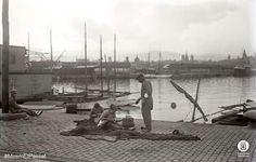 """Treballs de pescadors al Port de Barcelona. Al fons, """"skyline"""" de la ciutat cap al primer terç del segle XX. Fotògraf: Narcís Ricart i Bagués. Diputació de Barcelona"""