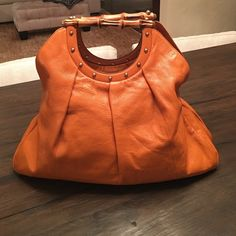 "Gorgeous GUCCI Handbag Absolutely gorgeous GUCCI Handbag in excellent condition. Bright orange supple leather with double bamboo handles and gold studs. Flawless lining with inside zipper pocket. 18"" wide 16"" tall 4"" deep 4.5"" handle drop Gucci Bags"