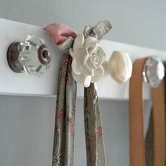 Cute doorknobs from Hobby Lobby, wooden board, and paint!  Voila!  Instant rack!