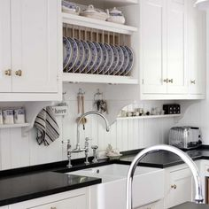 Pretty kitchen with beadboard backsplash, built-in plate rack, and small, under-cabinet wall shelves.