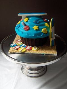 https://flic.kr/p/5axgYT | Giant Beach Themed Cupcake | Giant chocolate cupcake filled with chocolate ganache, covered in blue white chocolate fondant, and decorated with surf boards and sea creatures for a little boy's beach themed first birthday party.