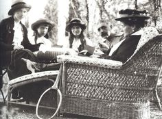 Olga, Anastasia, and Marie resting with Alexandra after a game of tennis.  Don't know who the gentleman is.