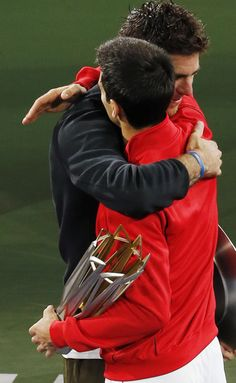 Serbia's Novak Djokovic, in red, and Juan Martin del Potro of Argentina, in black, embrace each other during the award ceremony of the Shanghai Masters tennis tournament at Qizhong Forest Sports City Tennis Center, in Shanghai, China, Sunday, Oct. 13, 2013. Djokovic won 6-1, 3-6, 7-6. (AP)