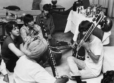 Musician George Harrison Receiving Sitar Lesson. Beatle George Harrison receiving instruction in playing the sitar from a Sikh teacher as the other members of the Beatles look on in quiet fascination. July 5, 1966. New Delhi, India.