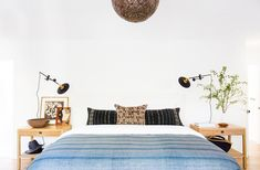 A calming and serene bedroom with modern table lamps, Moroccan chandelier, and blue throw