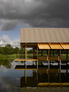 """The Fishing Hut by Niall McLaughlin Architects - """"By horizontally pivoting the shutters upward from the eaves the enclosure disappears, leaving you on a deck above the water beneath the pitched roof."""