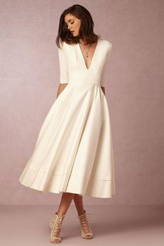 Great 50s inspired design, with sleeves; v-neck bodice, and eyelet detail on the A-line skirt, add modern touches to this classic gown. BHLDN Prospere Gown