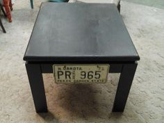 """For Sale: BLACK TABLE - This table  measures 28""""×231/2"""" and stands 191/2"""" tall.  It is a wood table,decorated with vintage license plates.  From a  non smoking shop.  Would be a conversation piece, one of a kind."""