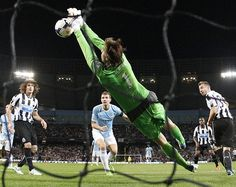 Newcastle United's Tim Krul saves a header from ManchesterCity's Edin Dzeko (centre) during their English Premier League soccer match at the Etihad Stadium in Manchester, northern England.