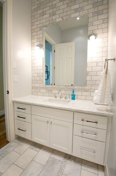 Gorgeous bathroom re-do.  Love the tile on the wall behind the mirror over the sink.