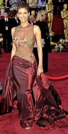 Halle Berry, 2002, Oscars, in a remarkable Elie Saab dress.  Classy and sexy in a deep burgundy with floral details barely covering the essentials left onlookers spellbound. Berry was the first black woman to receive the Oscar for Best Actress Award.