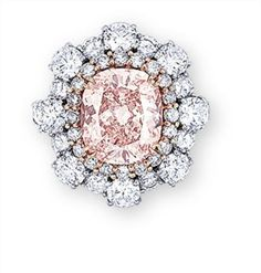 A COLOURED DIAMOND AND DIAMOND RING  Set with a cushion-shaped fancy natural coloured brownish orangy pink diamond weighing 3.03 carats, within a row of light pink diamonds and white diamonds.
