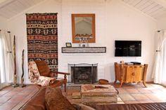 salon aménagé de style mexicain avec un tapis à motifs ethniques accroché au…