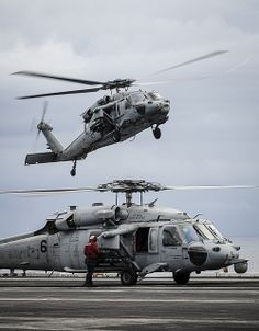 """SOUTH CHINA SEA (Nov. 20, 2013) Two MH-60S Seahawk helicopters, assigned to the """"Indians"""" of Helicopter Sea Combat Squadron (HSC) 6, land on the flight deck of the aircraft carrier USS Nimitz (CVN 68). Nimitz is deployed to the U.S. 7th Fleet area of responsibility supporting security and stability in the Indo-Asia-Pacific region. (U.S. Navy photo by Mass Communication Specialist Seaman Siobhana R. McEwen/Released)"""