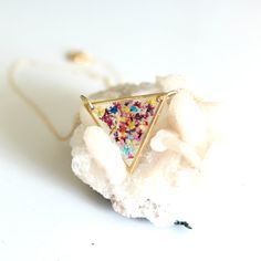 Teeny tiny pressed flowers scattered in between layers of crystal clear resin encased in a gold plated brass triangle setting. Comes on your choice of length 14k gold filled chain. This necklace is unique and each one is one of a kind so the placement of the flowers will be slightly different.