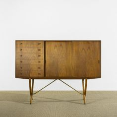 HANSWEGNER    cabinet    AndreasTuck  Denmark, 1952  teak, brass  66.25 w x 18.5 d x 49.75 h inches  Cabinet features six drawers and two sliding doors concealing three adjustable shelves and six shallowdrawers.