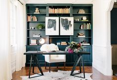 Built-in bookshelf with black and white artwork, white chair, dark grey desk, wood floors, and an accent rug