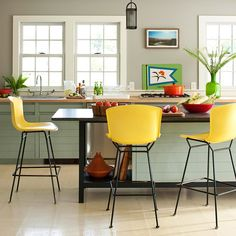 Beachy and Bright-These bright yellow barstools are authentic 1960s pieces. The bold color adds contrast to the neutral walls, floor, and island, and it relates to colors in the dishware on display. Other furnishings in bright green and red hues keep the space feeling sunny, just like the beach beyond the windows