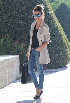 Black v neck top, rolled light denim skinny jeans, black heels, long camel trench coat, paired w sunglasses and messy bun. Cute easy fall or winter outfit